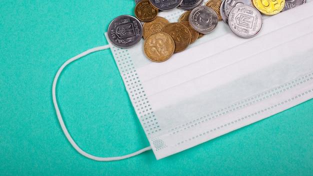 医療用マスク、防護マスク、青色の背景に一握りのコインの価格上昇。パンデミックコロナウイルスcovid-19による薬の価格の上昇。