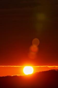 Rising of the sun in mountains redorange sun disk rises mountain natural lens flare in orange sky