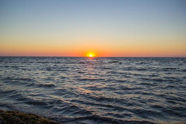 잔잔한 파도와 물에 반사 떠오르는 태양.