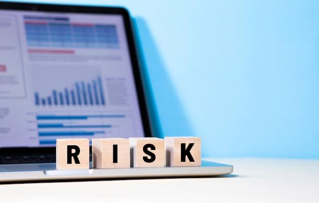 Концепции управления рисками и бизнесом с текстом на деревянной коробке на ноутбуке