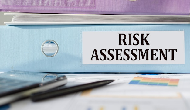 Risk assessment text written on folder with documents and calculator.
