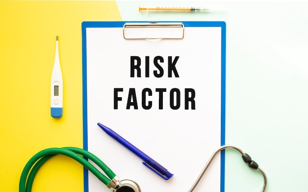 Risk factors text on a letterhead in a medical folder on a beautiful background. stethoscope, thermometer and pen.