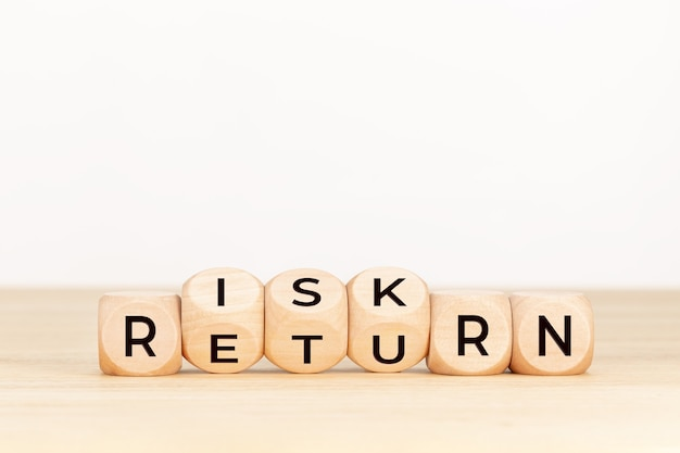 Risk return concept. wooden block with text on table.