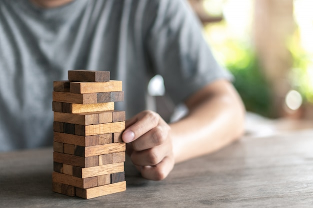 The risk will happen.hand of engineer playing a blocks wood game on wood