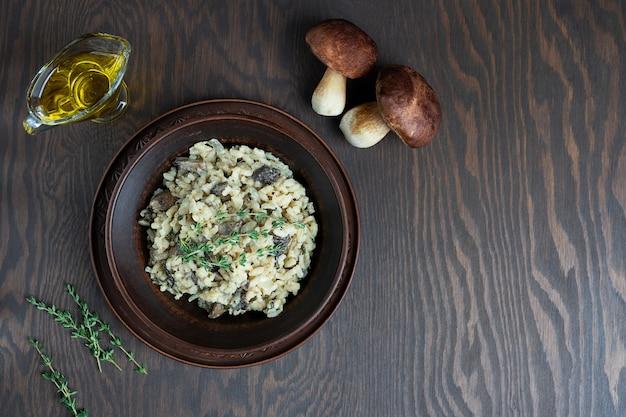 Ризотто с рисом арборио, бульоном, грибами и тимьяном на темно-коричневом деревянном столе