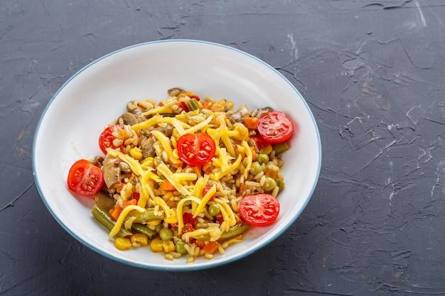 Ризотто с грибами и сыром и овощами в тарелке на сером фоне.