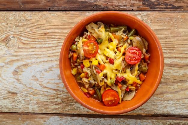 Ризотто с грибами и сыром в глиняной тарелке на деревянном фоне.