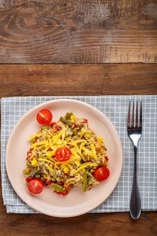 Ризотто с грибами в тарелке на деревянном фоне на клетчатой салфетке и вилке.