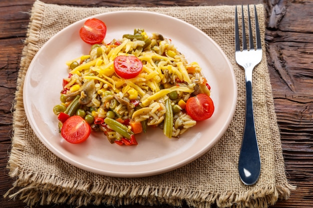 Ризотто с грибами в тарелке на деревянном фоне на льняной салфетке и вилке.