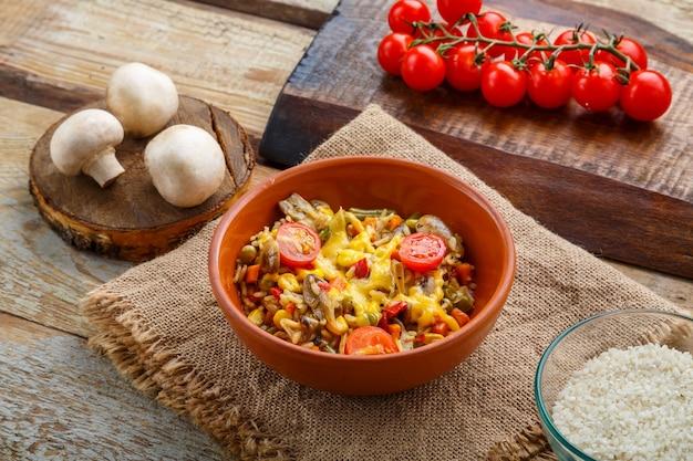 Ризотто с грибами в тарелке на деревянном фоне на льняной салфетке рядом с помидорами.
