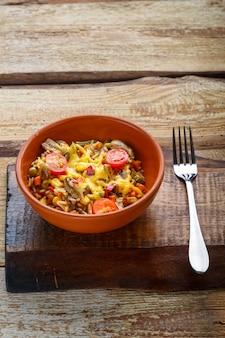 Ризотто с грибами в тарелке на деревянном фоне на деревянной доске рядом с вилкой