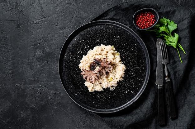 Ризотто с осьминогом и грибами, петрушкой и специями. вид сверху. пространство для текста