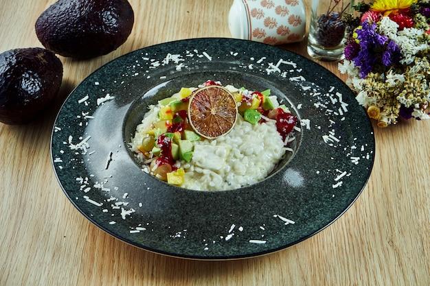 Ризотто с пармезаном, голубым сыром и авокадо в миску на деревянном столе. итальянская еда. изысканная еда. здоровая пища. закрыть