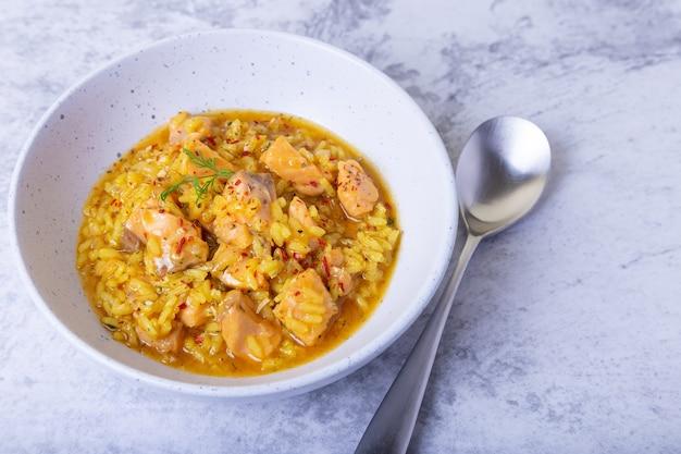 흰색 접시에 연어와 사프란 리조또. 전통 이탈리아 요리. 확대.