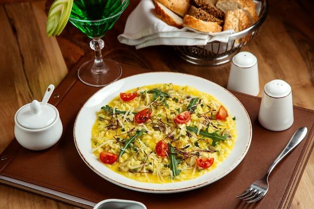Risotto with tomatoes mushroom cheese arugula tarhun lemonade salt pepper and bread on table