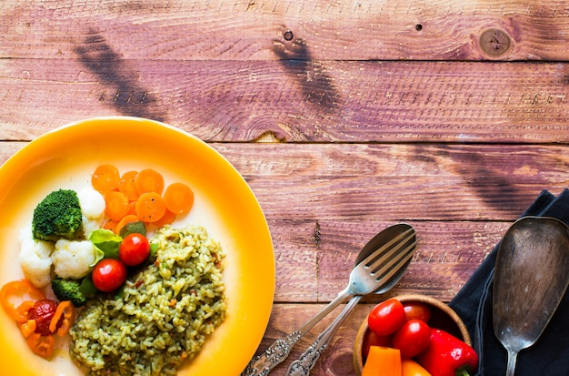 Risotto with vegetables, on wooden  background