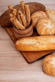 Ð¡risp 빵과 빵. 프랑스 바게트. 신선한 크리스프 브레드. 빵 배경. 나무 배경에 다른 품종입니다.