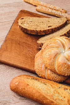Свежий хлеб с булочками. французские багеты. свежие хлебцы. фон хлеба. разные породы на деревянных фоне.