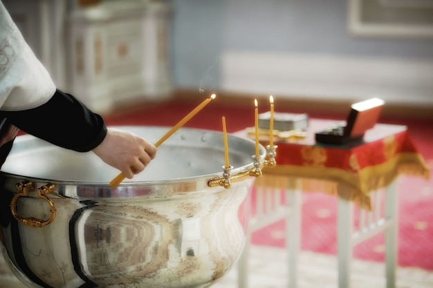 Rite of baptism in an orthodox church, priest lights candles at children's baptismal font. sacrament of orthodox baptism. closeup