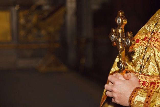 Обряд крещения золотой крест в руках священника в православной церкви или храме для церемонии пасхи