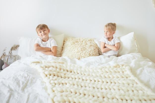 兄弟間の競争。大きなキングサイズのベッドの両端に座って、腕を組んで、お互いに話し合っていない2人のヨーロッパ人の兄弟の屋内画像。子供と家族の概念