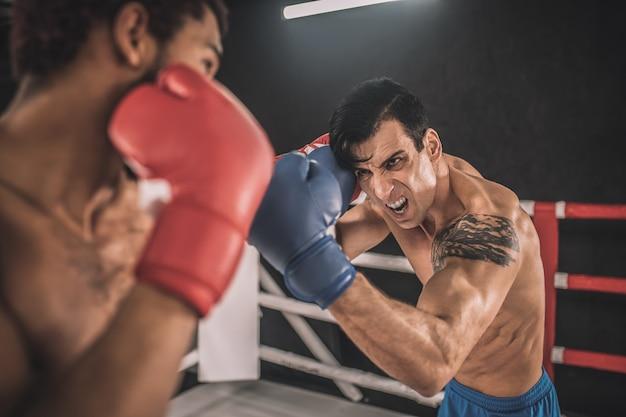 Соперничество. два кикбоксера дерутся на боксерском ринге и выглядят агрессивно