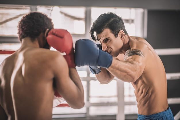 Соперничество. два соперника борются на боксерском ринге и выглядят агрессивно
