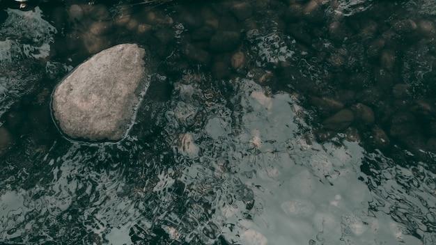 暗いトーンで川と岩の背景。