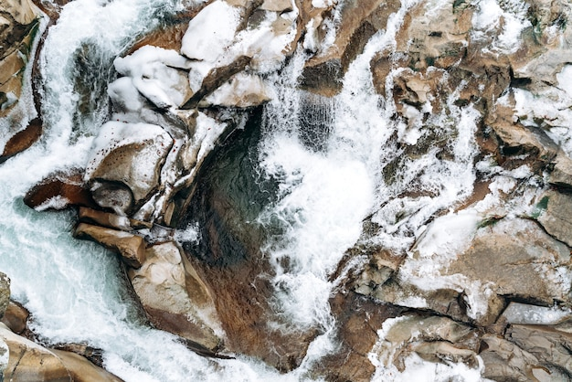 山の川。澄んだ渓流の底にある岩の上面図。茶色の岩と荒れた水。ストックフォト