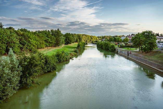 프랑스 카르카손의 오드강 푸른 강둑과 잔잔한 시내