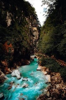 昼間の茶色と緑の岩山の間の川