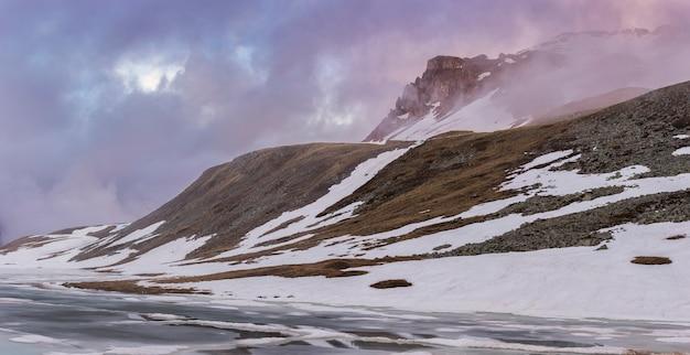 Река покрыта снегом и льдом с горами на заднем плане в альпах.