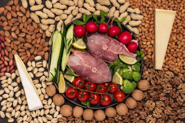 강물고기, 체리 토마토, 오이, 레몬, 브로콜리, 로즈마리가 검은 접시에 있습니다. 테이블에 치즈와 견과류입니다. 플랫 레이