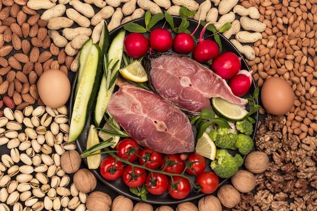 강물고기, 체리 토마토, 오이, 레몬, 브로콜리, 로즈마리가 검은 접시에 있습니다. 테이블에 치즈, 계란, 견과류. 플랫 레이. 확대