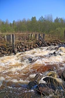Река течет по старой разрушенной плотине