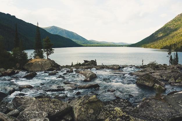 Речной поток с огромным камнем. река впадает в мультинское озеро. шум между двумя озерами. алтай россия