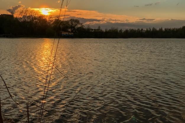 River flows at sunset, sun rays illuminate the ripples on water surface