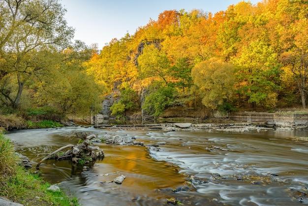 Осенняя река со старой сломанной плотиной, деревьями и скалами по бокам, длинная выдержка, стрибро