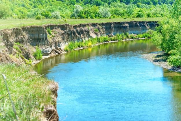 푸른 물, 숲, 가파른 해안이 있는 산의 강