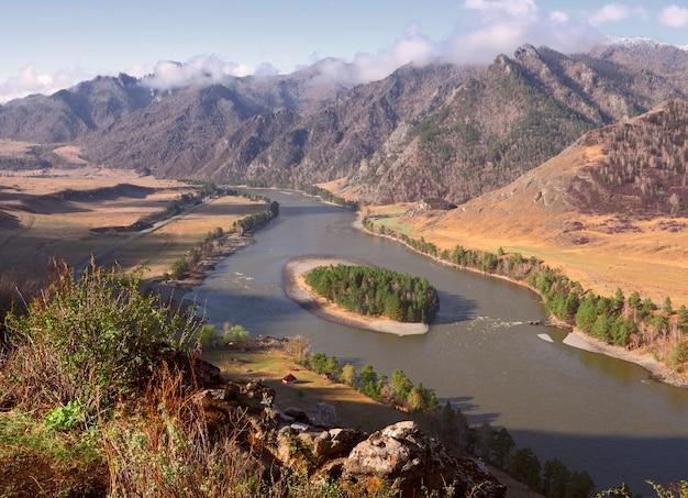 Река в горах алтая цветущая трава на скалах остров на берегу реки с берега