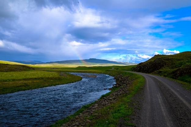 Река посреди дороги и травянистое поле с радугой на расстоянии в дневное время