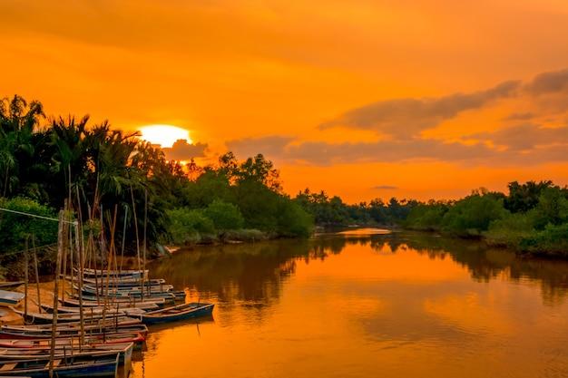 해질녘 열대우림에 있는 강. 해안에서 여러 보트
