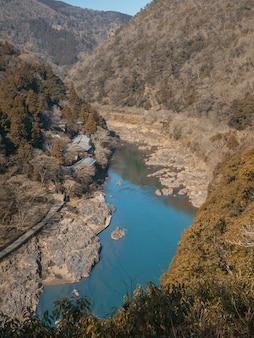 Река в долине посреди леса осенью.