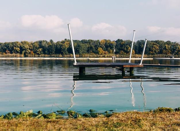 수상 스포츠를 위한 케이블 공원의 일부인 나무 무대가 있는 강 풍경