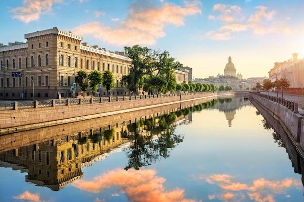 Река мойка в санкт-петербурге с зеркальными отражениями зданий на набережной и исаакиевского собора в лучах рассветного солнца