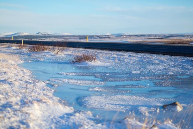 Река на равнине в исландии. берега засыпаны снегом. зимний пейзаж, просторы.