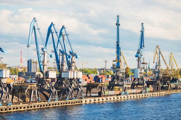 Речной порт в городе рига. большие краны для перевозки грузов в порту. тяжелая промышленность в латвии. грузоперевозки в доке. индустриальный пейзаж. коммерческий импорт товаров