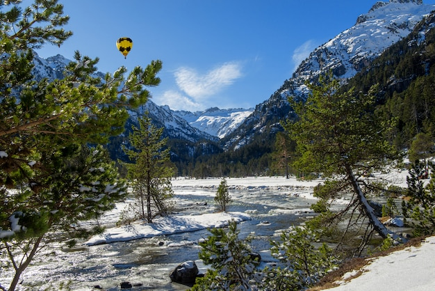 River in the snowy pyrenees mountains with yellow hot air balloon
