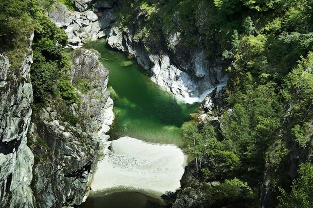 햇빛 아래 큰 산으로 둘러싸인 강