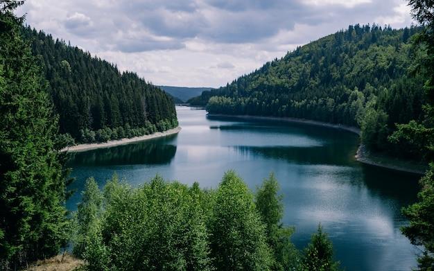 독일 튀 링겐의 흐린 하늘 아래 숲으로 둘러싸인 강
